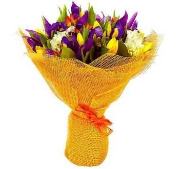 Букет в желтой упаковке с тюльпанами, фрезиями, ирисами и зеленью