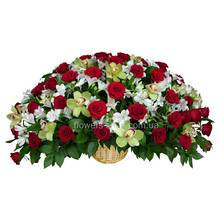 Композиция в корзине из красных роз, орхидей цимбидиум, альстромерий и зелени рускуса