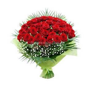 Букет в декоративной упаковке из красных роз, гипсофилы и листьев феникса