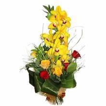 Букет с веткой орхидей цимбидиум, розами и зеленью рускуса и аспидистры, упакованный в сетку