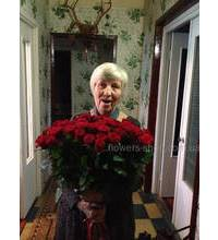 Женщина с букетом красных роз в момент доставки
