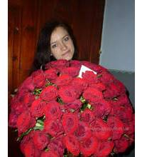 Жінка тримає великий букет троянд