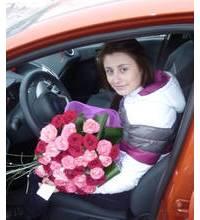 Букет роз с зеленью и в сетке в руках у автомобилистки