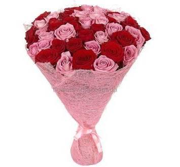 Круглый букет из красных и розовых роз в упаковке