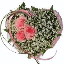 Композиция в форме сердца из розовых роз, гипсофилы, зелени ледерварена и берграсса