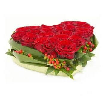 Красные розы, гиперикум, листья аспидистры на флористическом оазисе
