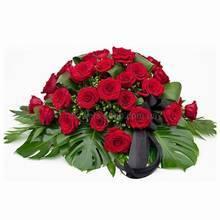 Композиция в кашпо из красных роз, гиперикума, листьев монстеры и аспидистры